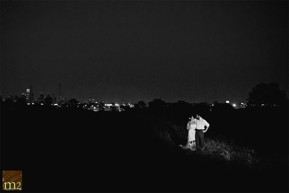 Bride and groom night portraits with city skyline